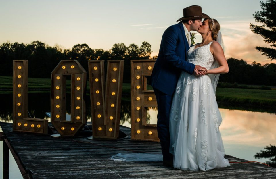 Bride and groom kissing on the dock of a pond at sunset on family farm in Waterford, PA