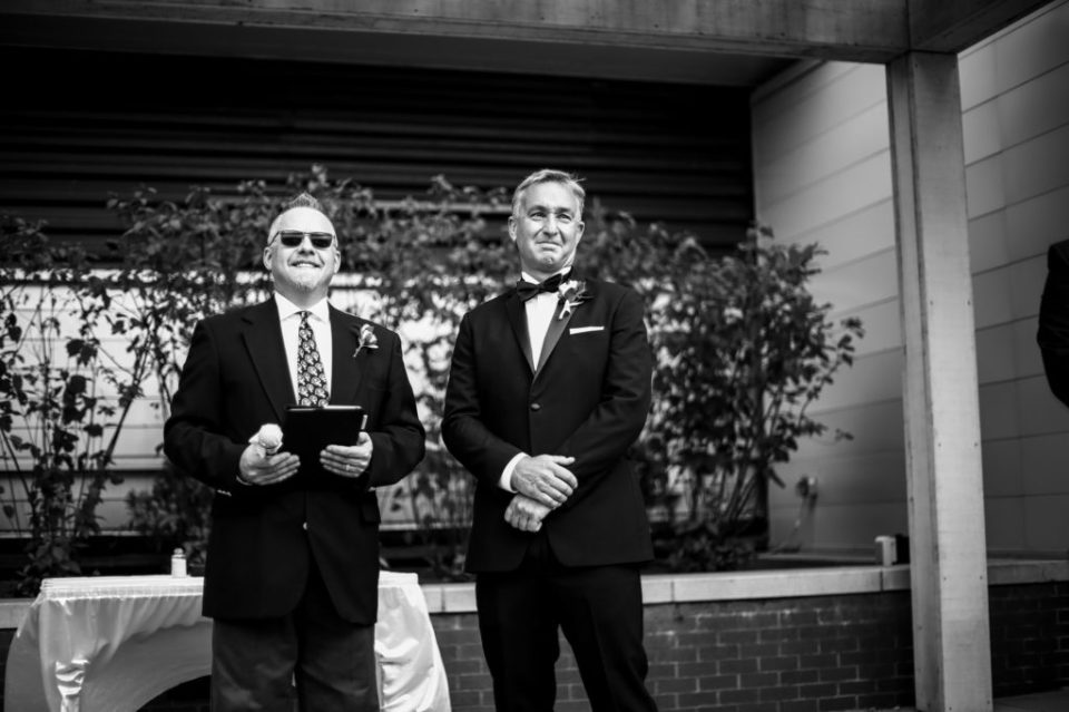 Groom smiles as he watches bride walk down the aisle at Anchor Plaza wedding in Erie, PA