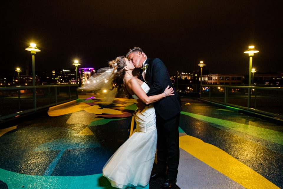 Bride and groom kiss on the platform of the BIcentennial Tower at night