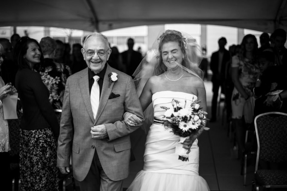 Bride smiling ear to ear as father walks her down the aisle at Anchor Plaza wedding in Erie, PA