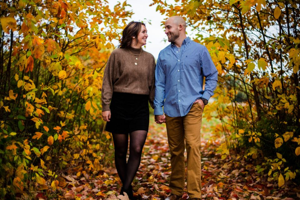 Couple walks through fall leaves on family property in Girard, PA