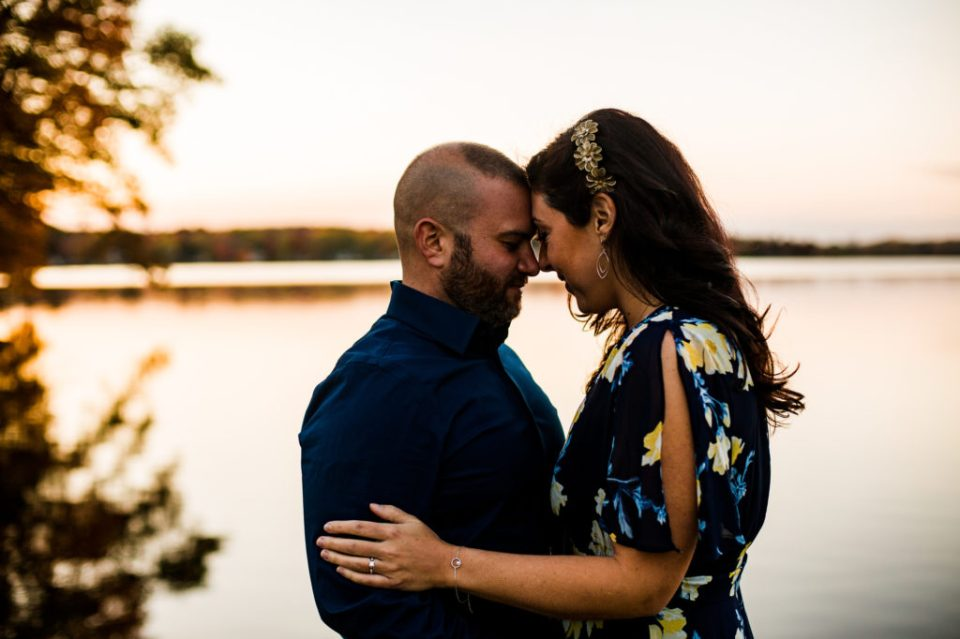 Engaged couple touch foreheads and embrace next to the lake for Edinboro PA engagement photos