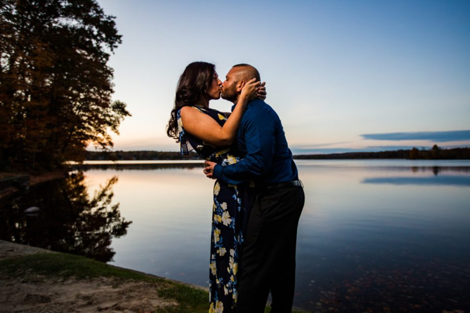 Man and woman kiss at sunset on Edinboro Lake for Edinboro PA engagement photos