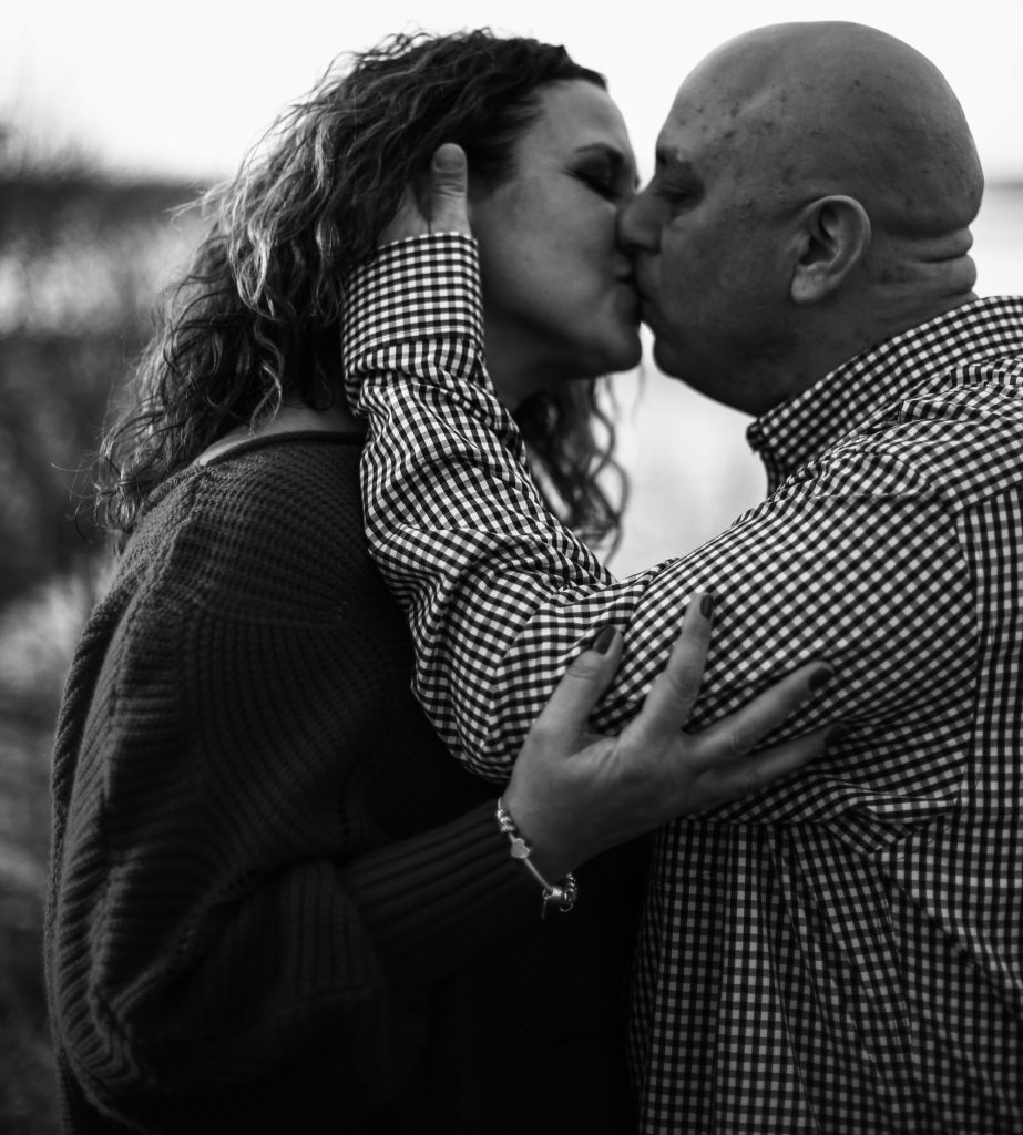 Man runs fingers through fiancee's hair as they kiss during engagement photos in Erie, PA