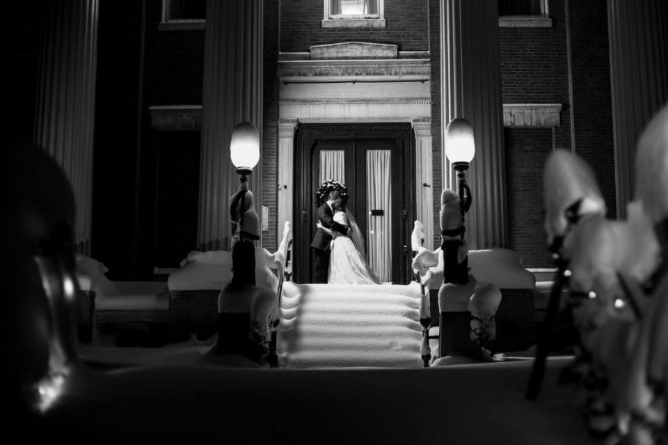 Bride and groom embrace in the snow outside the Erie Club doors