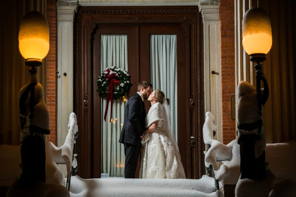 Couple kissing in the snow outside the Erie Club's doors
