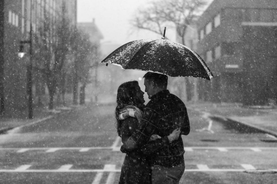 Man and woman embrace under an umbrella as snow falls during winter engagement photos on Gannon University's campus in Erie, PA