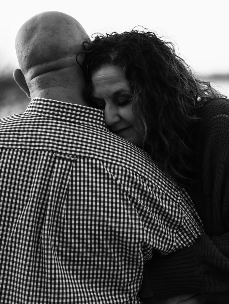 Woman, with eyes closed, hugs her fiance and smiles