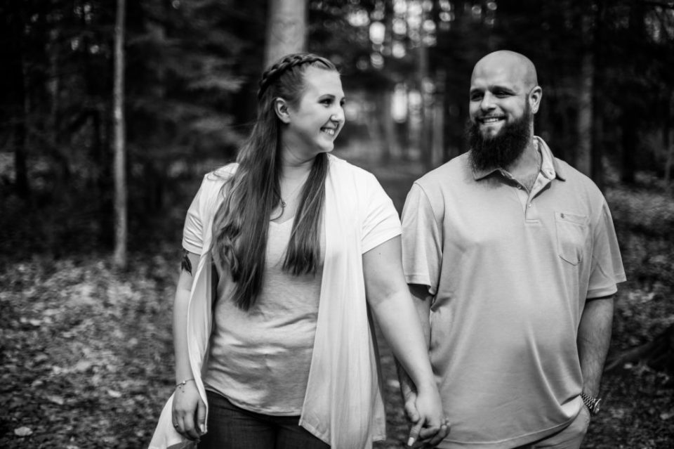 Smiling couple walks through Asbury Woods for engagement photos
