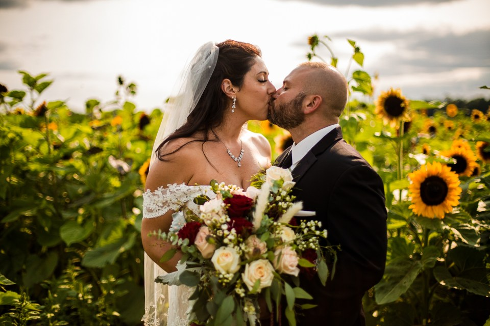 Couple kissing in the sunflower field at Port Farms