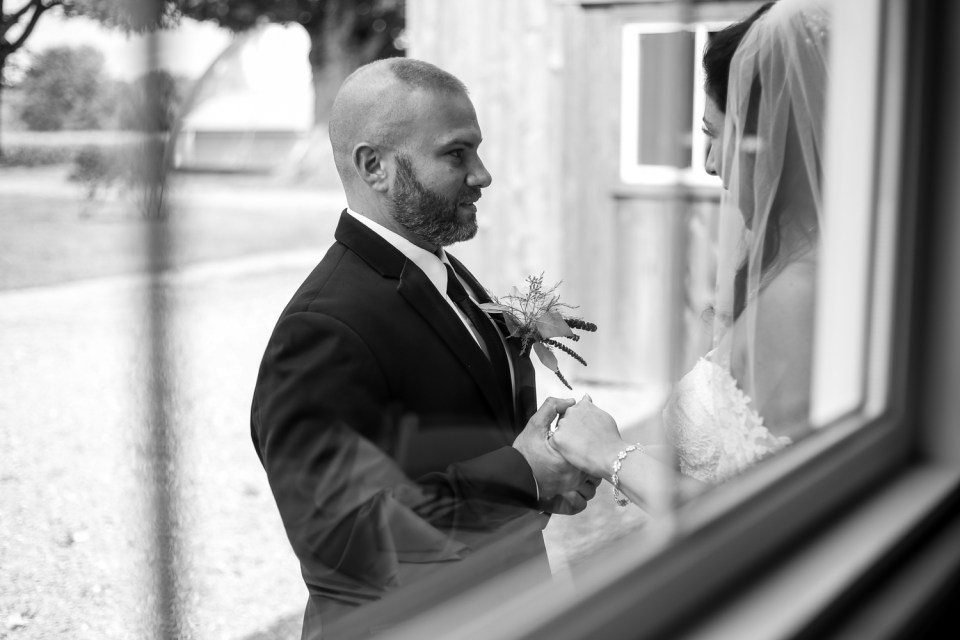 Groom holds bride's hands during first look photo at Port Farms wedding
