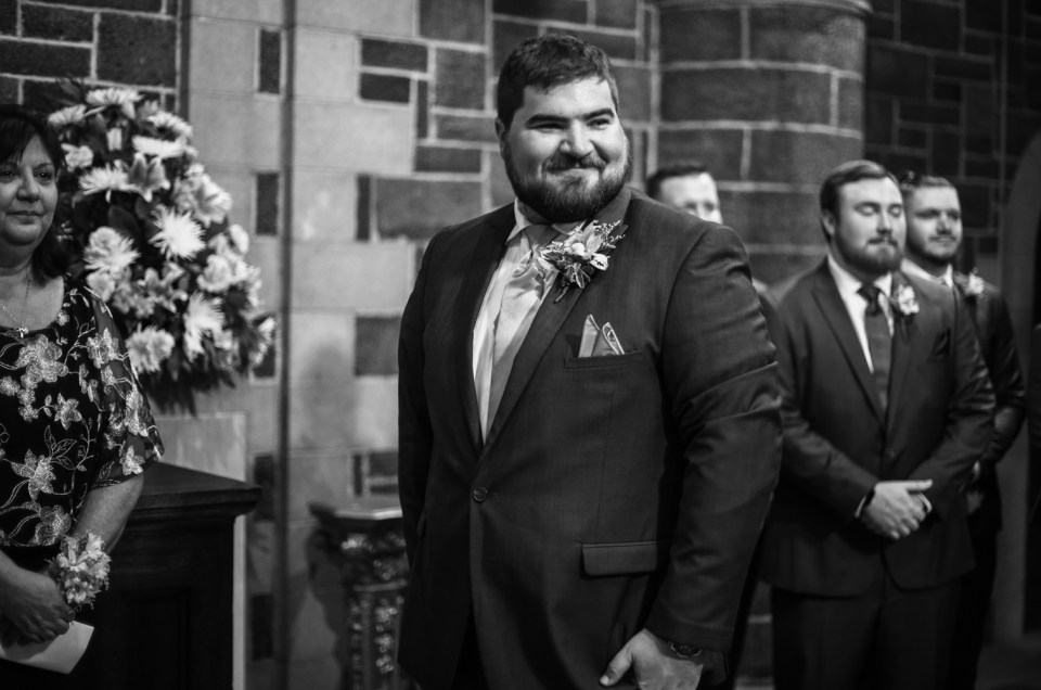 Groom smilies as he watches bride walk down the aisle of the chapel at Beach Glass Estates