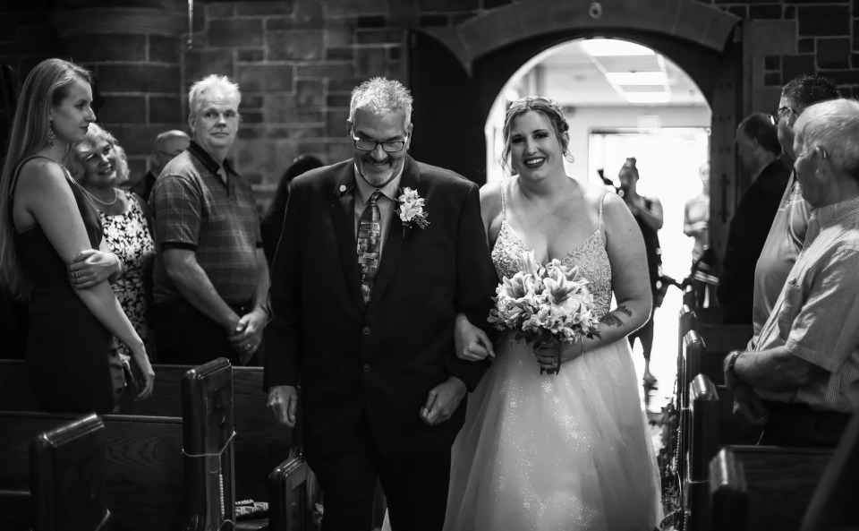 Smiling bride escorted by her father at Beach Glass estates wedding