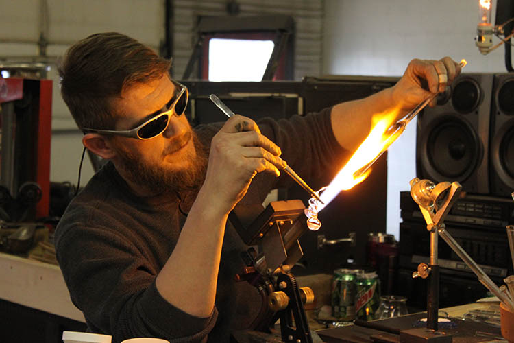 Chad Christensen melting glass with his torch.