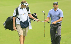 A golfer walking with a caddy