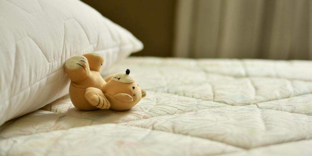 Teddy bear and a pillow at the top of the foam mattress