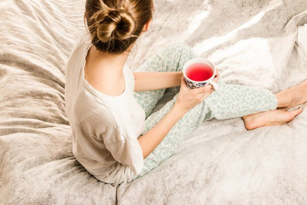 lady in a bed room is holding a cup of beverage