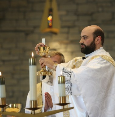 Fr. Matt elevates the Body and Blood of Christ