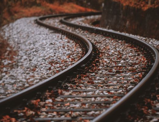 image of railway tracks close up in autumn snaking into distance