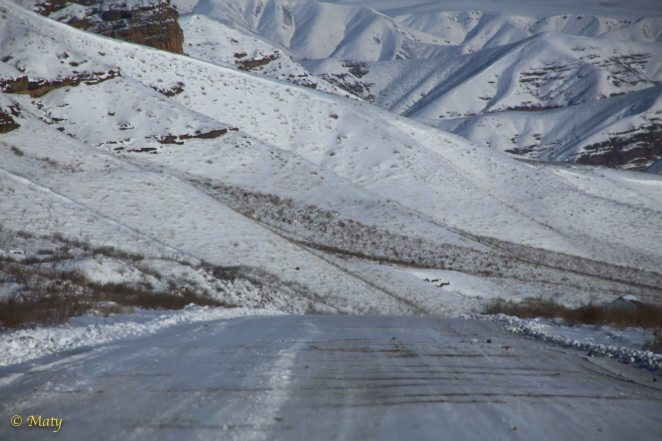 On the road there is compressed layer of snow, then some gravel and then accumulating ice...