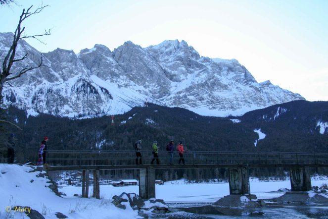 Walking on the small bridge over frozen Frozen Eibsee Lake