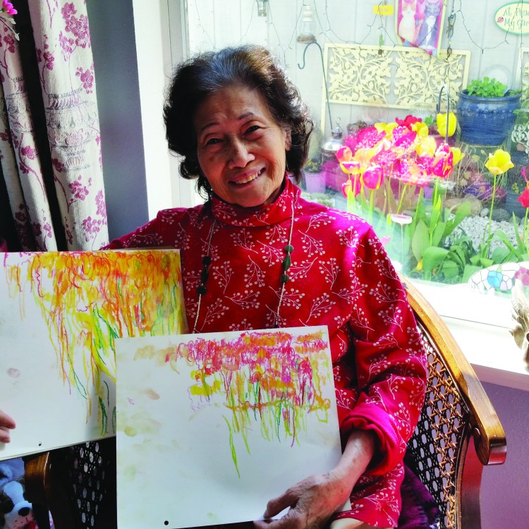 A smiling woman wearing a read top sits in a chair by a window while holding colorful paintings. Image courtesy of 2020 Awardee Trang Tu.