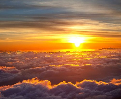 Sun coming up over the clouds during the Haleakala Sunrise Tour