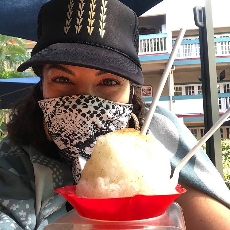 Malika Dudley eats shave ice in Maui with black and white mask