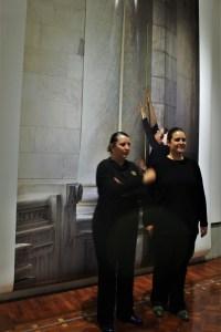 Las fotógrafas Francisca Rivero-Lake Cortina y Carla Verea Hernández posando junto a una de las fotografías para demostrar la proporción de cada una de las piezas en la exposición Uno a uno/Bellas Artes. Lake Verea.