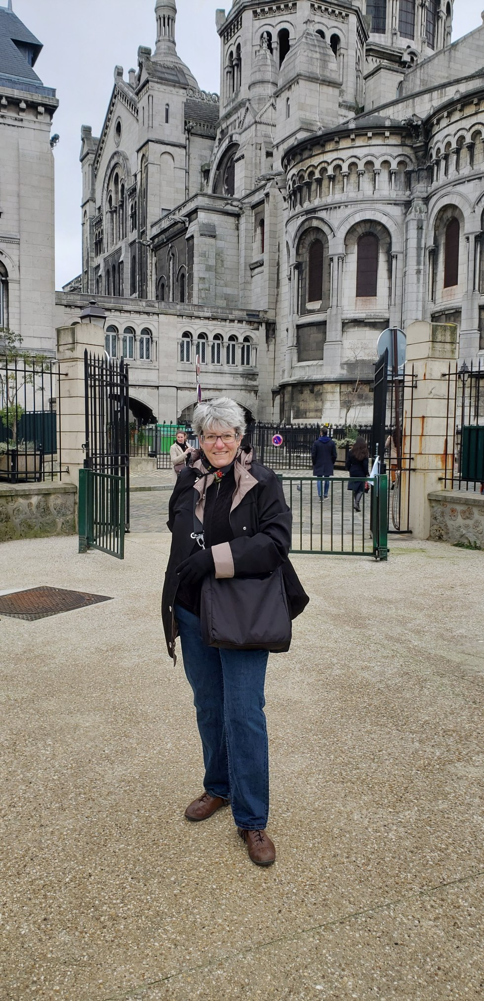 Artist Maura Satchell standing in front of the gates of the Louvre