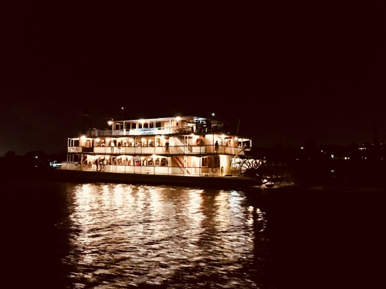 Old paddle steamer boat on the Brisbane River at night with the lights from the boat reflecting on the water