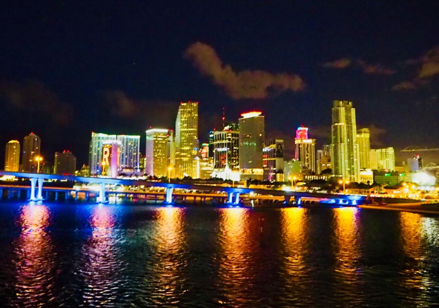 Buildings in Miami Florida lit up at night with the light shining on the harbour