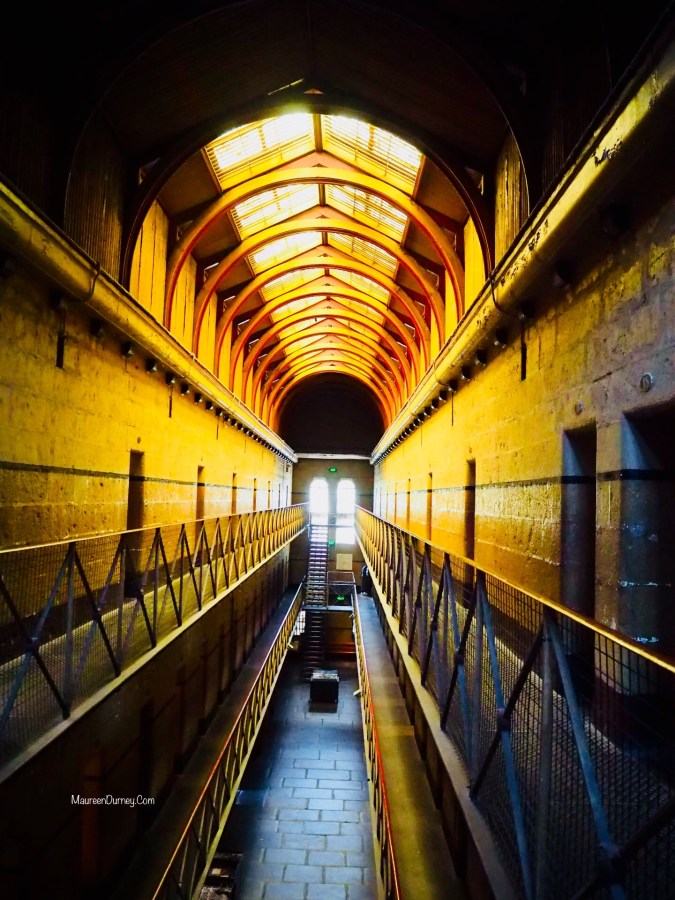 Inside Old Melbourne Gaol with cell doors each side and skylights above.