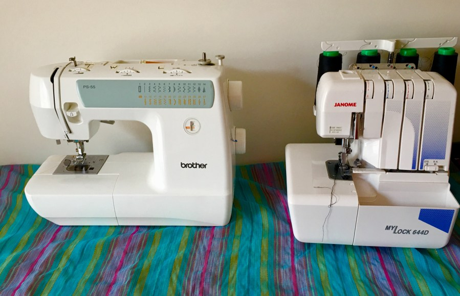 Sewing machine and overlocker sitting on colourful striped fabric on top of table