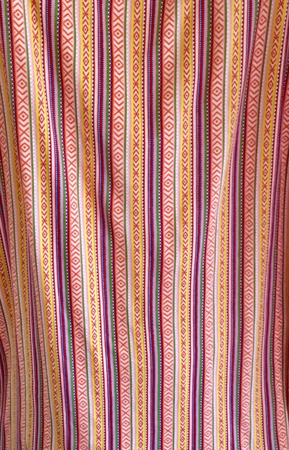 Stripy fabric with arrow type designs, mostly orange, yellow, green, red and blue colours.