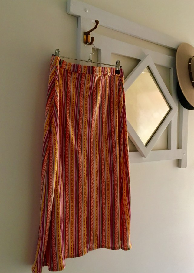 Striped skirt hanging on a white mirror against a wall background. The skirt is mostly yellow and orange colours.