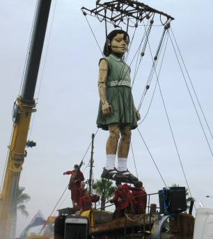 Little Girl is lifted up by a waiting crane.