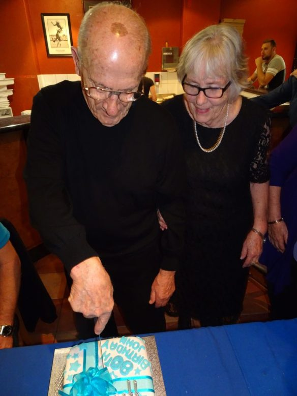 John cuts his cake at a party with my family
