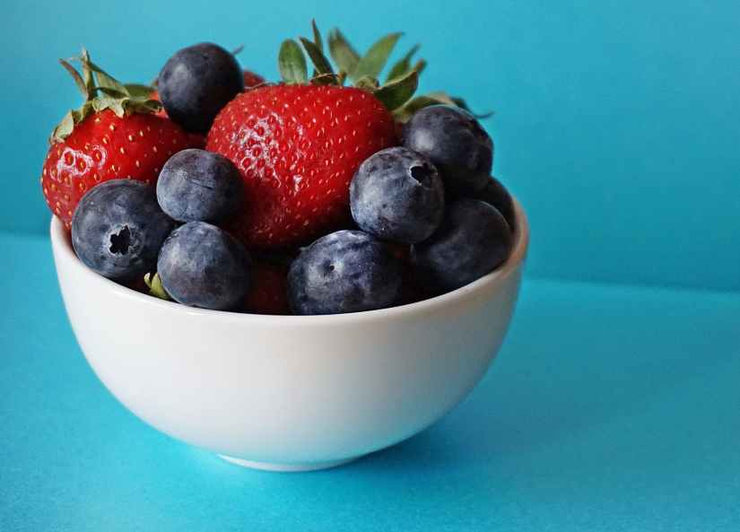 Health food blueberries and strawberries in white ceramic bowl