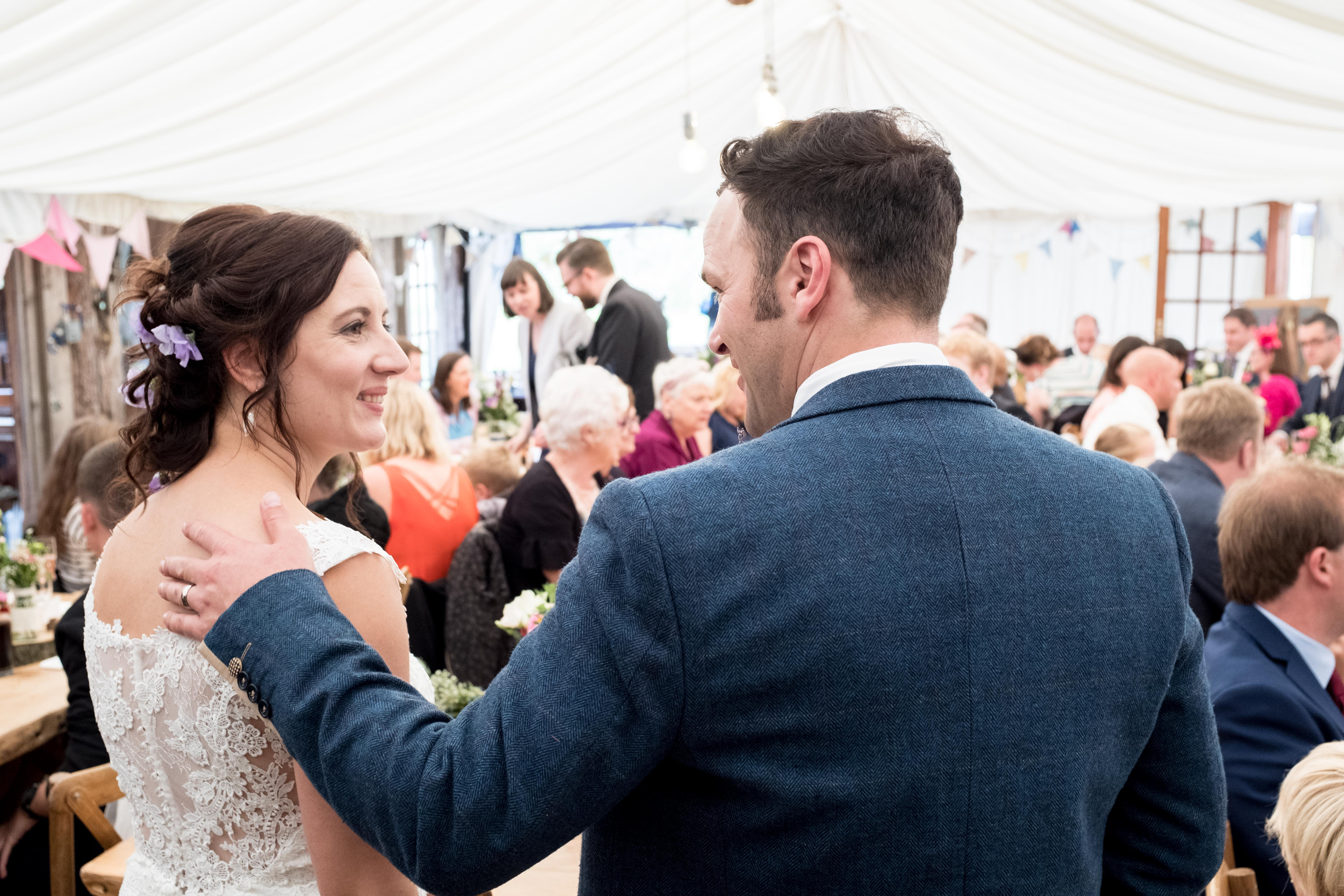 Jo and Rhys smile at each other at their wedding at King Acres in Chester