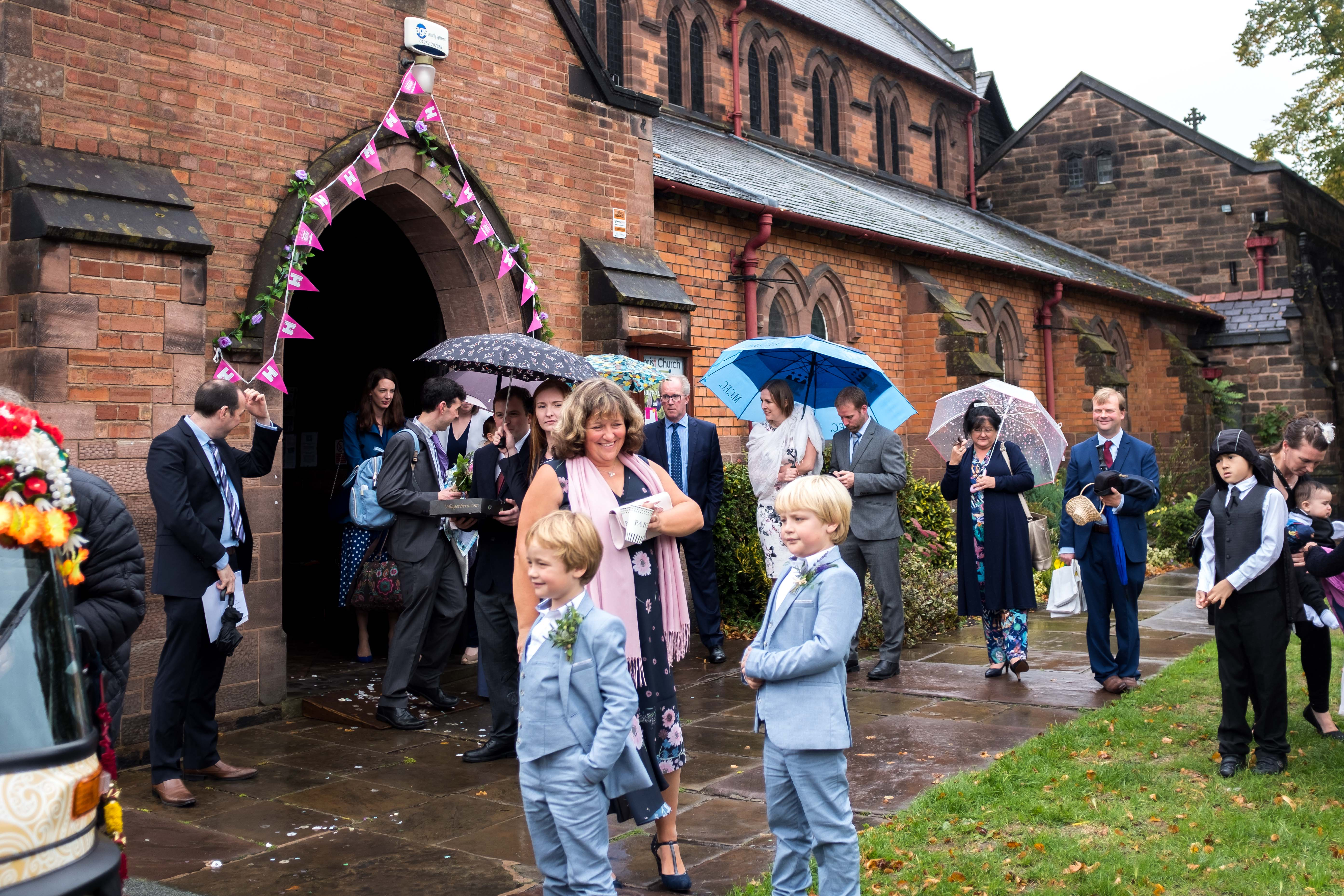 Wedding congregtion wait in the rain for the bride and groom to come out