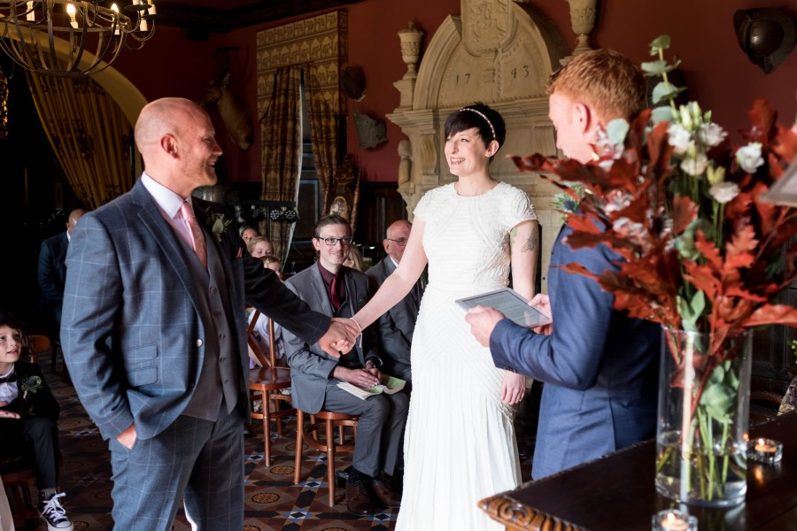 Trevor Hall wedding ceremony in North Wales. Bride and groom holding hands.