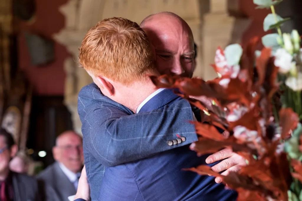 Grrom and best man hug at Llangollen wedding ceremony
