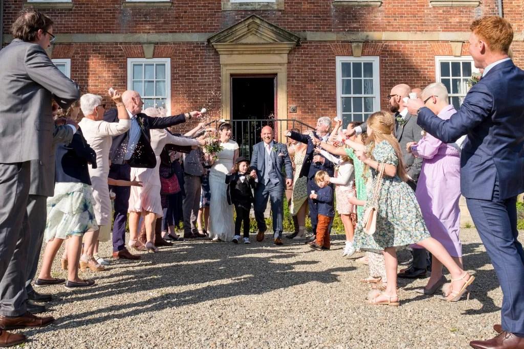 Confetti throw at Trevor Hall wedding Llangollen. Bride and groom getting showered in confetti.