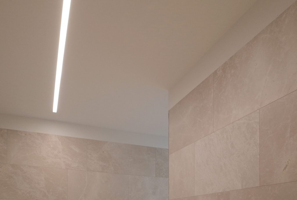 Architectural design of bathroom with mirrors and led strips and nature stone