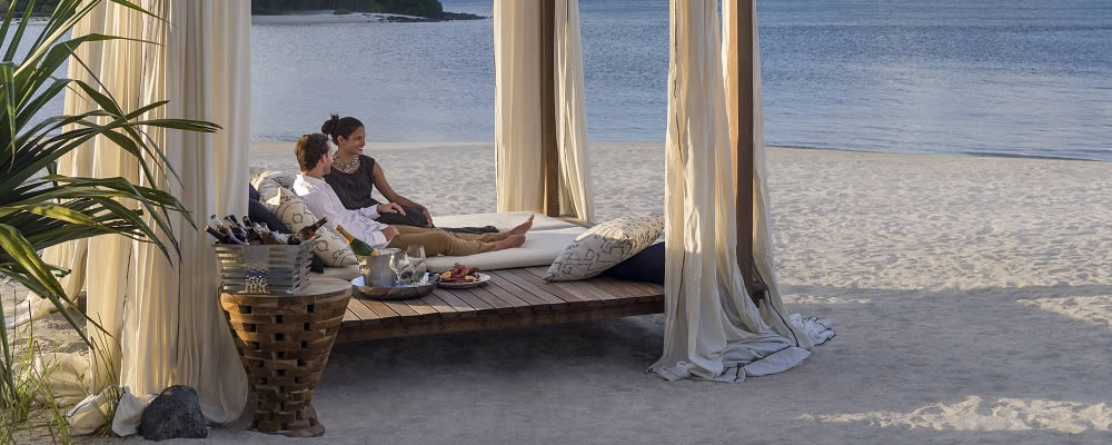 Couple relaxing on a cabana on the beach at Le Touessrok