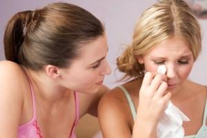 A teenage girl comforting her friend
