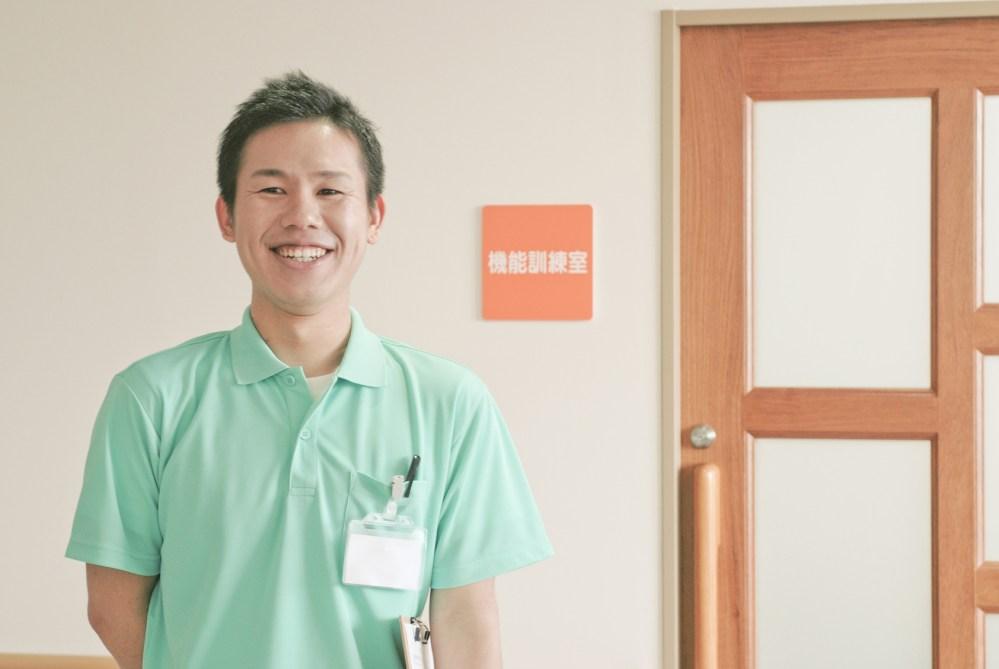 機能訓練室の前に立つ笑顔の男性理学療法士