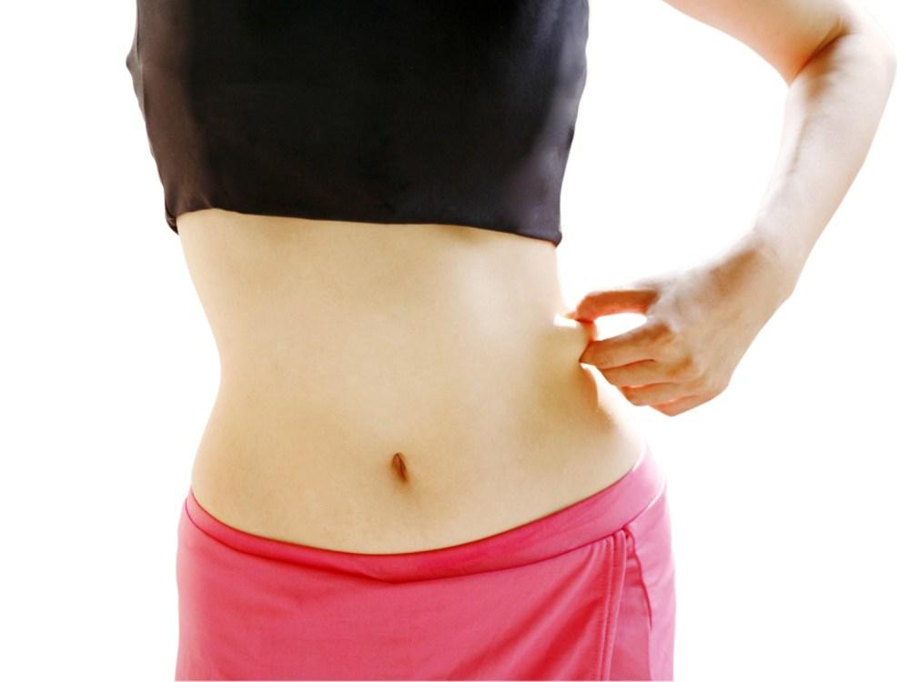 脇腹の脂肪を摘まむ女性