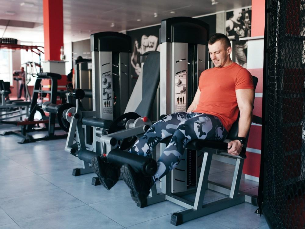 筋トレ器具で足を鍛える男性